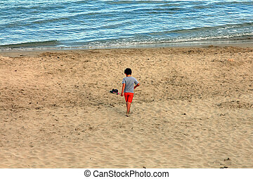 beach with a small child walking red trousers