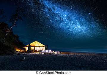 Beach with glowing tent at night with stars