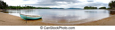 panoramic view of beach of scandinavian lake, with moored wooden rowboat