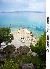 Beach with palm sunshades in Croatia
