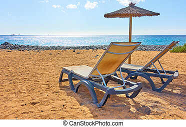 Beach with parasol and chaise longues by the sea