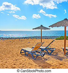Beach with parasol and chaise longues