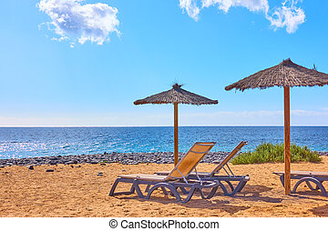 Beach with parasols and chaise longues by the sea