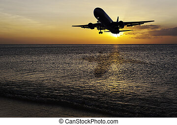 Beach with plane on color of the sunset