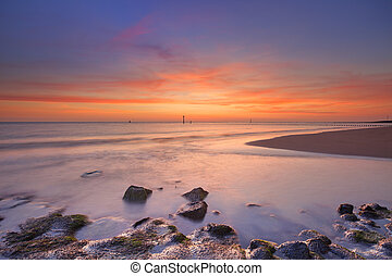 Beach with rocks at sunset in Zeeland, The Netherlands