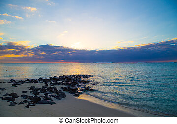 Beach with rocks at sunset - Beach with black stones at...