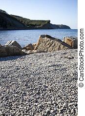 Beach with sand, round stones, selective focus