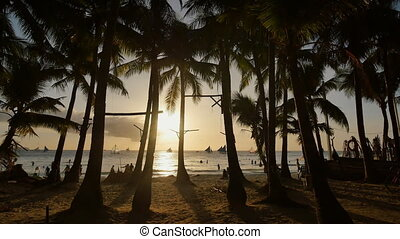 Beach with silhouettes of tourists among palm trees on the island of Boracay. Palm trees in the rays of sunset. Sailboats on the water. Philippine Tropics.