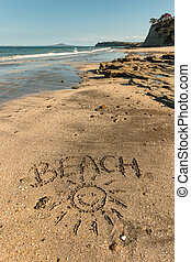 beach with smiley written in sand