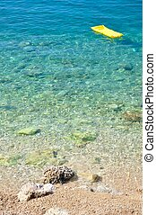 Beach with stones and yellow airbed