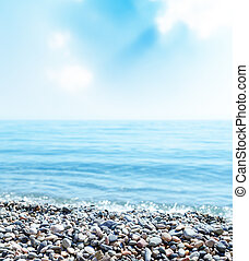 beach with stones, sea and blue sky with clouds