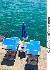 Beach with two sunbeds by the sea