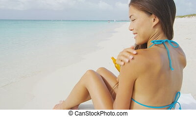 Beach bikini woman applying sunscreen lotion on body and shoulders. Asian multiracial girl model putting suntan oil spray for tan holding plastic bottle lying on beach on summer travel vacation.