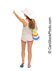 Beach woman pointing on copy space . rear view