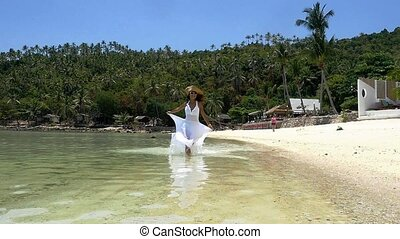 Beach woman running near water in long white dress and hat enjoying freedom during summer holidays vacation travel. Slow motion. 1920x1080. hd