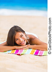 Beach woman thinking looking up at copyspace. Multiracial Asian Chinese / Caucasian female girl relaxing on beach towel smiling happy