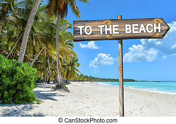 Beach Wood Sign with text To The Beach, Palm Trees, Tropical See and Blue Sky