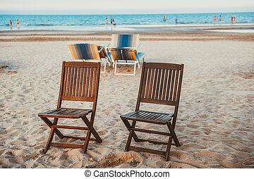 Beach wooden chairs on the sand