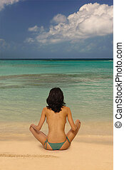 Beach Yoga - Back of a beautiful, young woman doing yoga on ...
