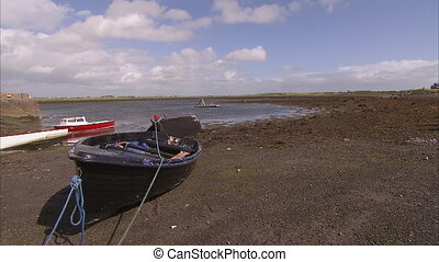 Beached row boat with beautiful landscape - A black beached...