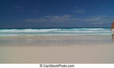 beachwalk together - senior couple walking along sandy beach...