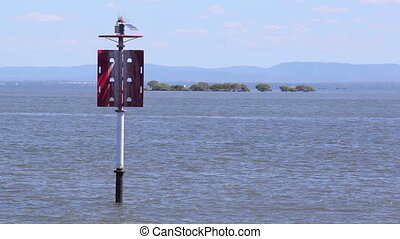 Beacon With Boat - Two speed boats pass behind a red beacon...