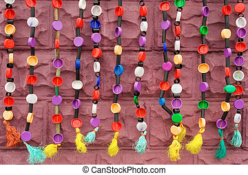 Strings of ethnic beadwork hanging against a wall