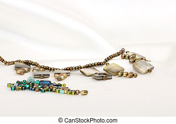 Beading - Beaded necklace with assorted beads on white satin
