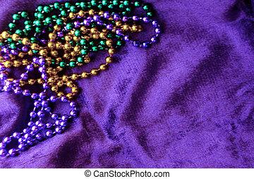 Green, gold, and purple beads on purple velvet