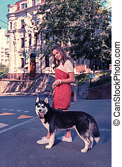 Beaming appealing woman standing near her dark blue-eyed husky dog