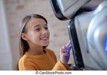 Beaming cute girl programming her house robot