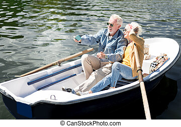 Beaming elderly lady posing for photo with her husband in boat