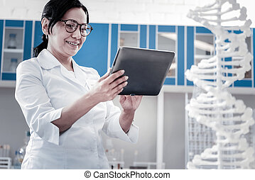 Beaming female scientist using tablet computer in laboratory...