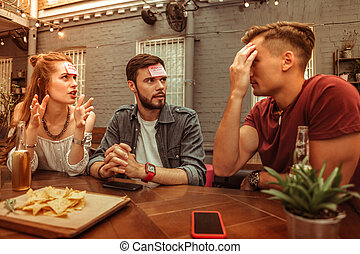Beaming friends enjoying playing a hedbanz game at the bar