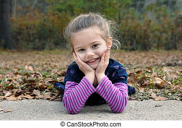 Adorable little girl lays on the Fall leaves and leans her head in her hands. She is smiling and beaming. She has on a navy shirt with purple striped sleeves.