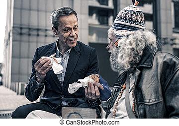Communicative kind man talking to grey-haired senior homeless