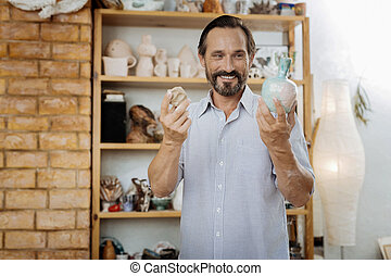 Beaming inspired man working in his workroom making vases