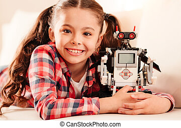 Beaming little girl embracing her new robot toy