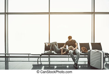Beaming lovers relaxing on bench in hall