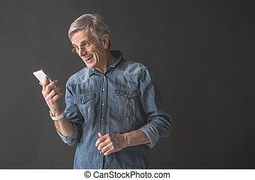 Beaming mature male using modern cellphone