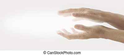 Pair of female hands held parallel on a light background with white energy between palms