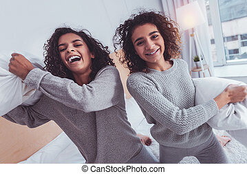 Beaming sisters feeling cheerful relaxing together