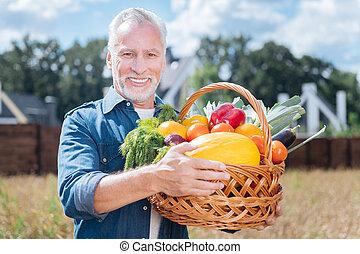 Beaming smiling bearded man holding nice big basket with fresh vegetables