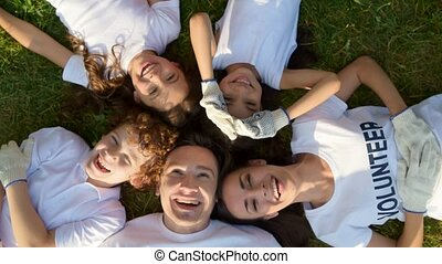 Beaming volunteers lying head to head on grass - Spending...