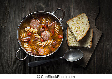 Bean stew - Fresh bean stew with sausage and pasta on wooden...