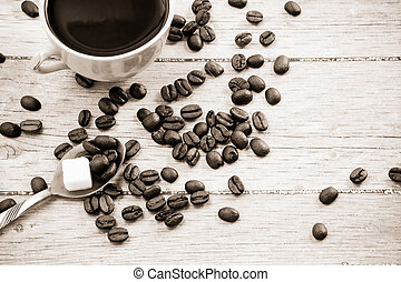 beans and cup of coffee on wood board