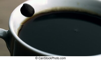 Beans falling into cup of coffee