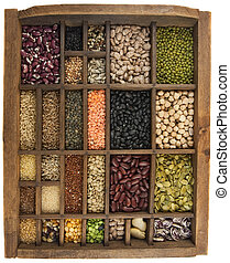 vintage, wooden typesetter case (drawer) with variety of beans, lentils, peas, grains and seeds isolated on white, white angle view