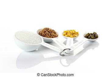 Beans in measuring spoons on white background