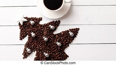 Beans in shape of fir and cup of coffee - From above view of...